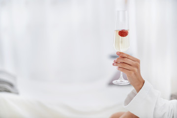 Tasty beverage. Close up of champagne with strawberry in girl arm. Copy space in left side