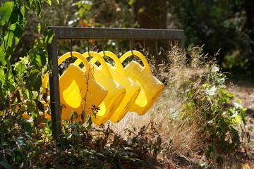 Gelbe Gieskannen auf Friedhof