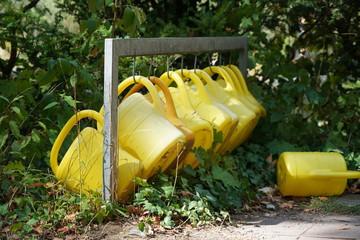 Gelbe Gieskannen in Reihe auf dem Friedhof
