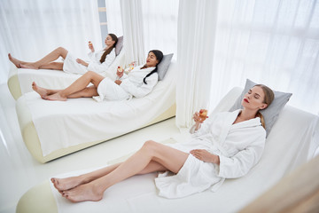 So sleepy. Beautiful young women in bathrobes lying on daybeds. They holding glasses of champagne...