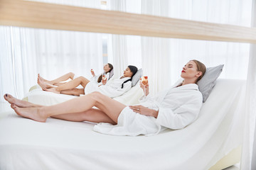 Perfect vacation. Lovely girls with closed eyes lying on daybeds at beauty salon. They holding glasses of champagne and resting