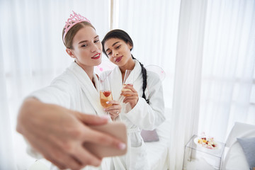 Unforgettable event. Smiling young woman in cute diadem taking photo with best friend. Ladies holding glasses with champagne