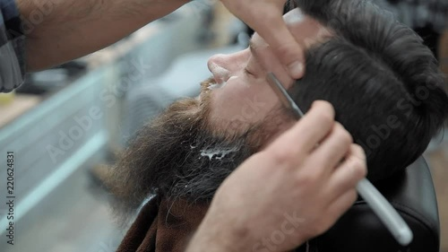 """Barber shaves men with a long beard with straight razor blade in s hair salon or barbershop. Man's haircut and shaving at the hairdresser, barber shop and ..."