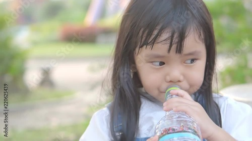 Asian Child Cute Or Kid Girl Thirsty And Drinking Cold Water In Plastic Bottle By Tube For Healthy And Refresh On Summer Holiday Travel At Public Park And