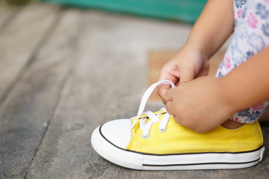 hand of children or kid girl learning and try tie shoelace on yellow shoe or sneakers rope and footwear for walk travel and fashion on street with independent and free