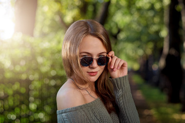 An attractive woman throws a glance through her glasses.