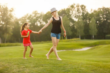 Happy family walking on grass fields. adorable little girl hold her mom hand walking