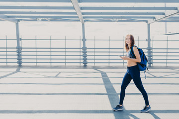 Outdoor shot of beautiful woman wth slim body, dressed in casual top and leggings, carries bag, going in gym, uses modern smart phone for listening music, copy space aside for your advertisement