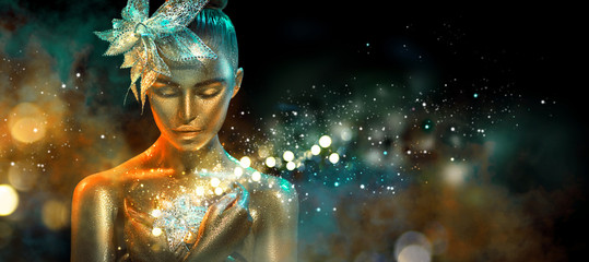 Fototapeta Fashion model woman in colorful bright golden sparkles and neon lights posing with fantasy flower. Portrait of beautiful girl with glowing makeup obraz