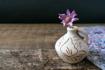 One lilac flower Xeranthemum on clay vase on wooden texture background close up. Wabi Sabi, Hygge, Lagom style. Loneliness, simplicity, minimalism concept