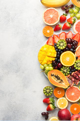 Wall Mural - Colorfult raw fruits berries, mango, oranges, kiwi strawberries, blueberries grapefruit grapes, bananas apples on white plate, on off white table, top view, copy space, vertical
