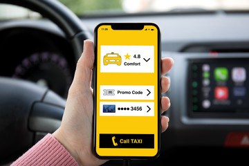 women hand holding phone with app call taxi on screen