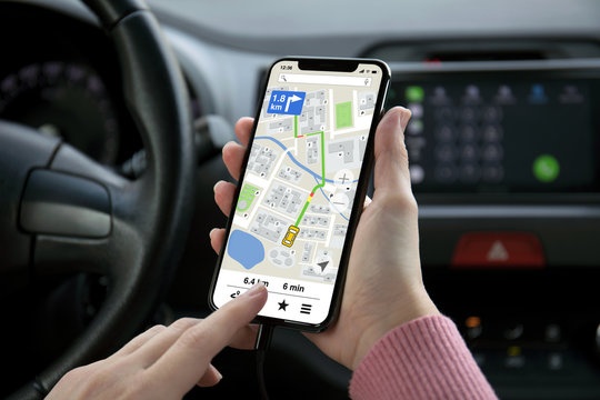 women hand holding phone with app navigation map on screen
