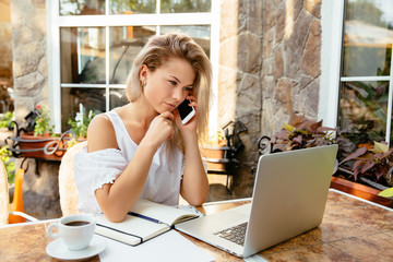 Freelance business. Concentrated beautiful blond businesswoman calling by smartphone, while looking at laptop screen, woman sitting at the cafe table with cup of coffee. Outdoors