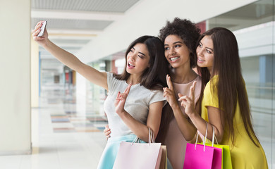 Happy women taking selfie while shopping in mall