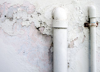 close-up two white water pipes on dirty old and peeling white concrete wall, pvc drainage tube and plumbing pipe outside the building with connected from within