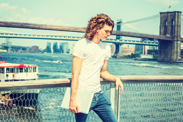 Hispanic American Man traveling in New York, with long curly hair, wearing white T shirt, holding laptop computer, standing by East River, thinking. Manhattan, Brooklyn Bridges, boat on background