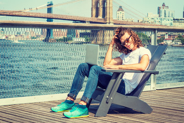 Young Hispanic American Man traveling in New York, with long hair, wearing sunglasses, white T shirt, jeans, sneakers, sitting on chair by river, working on laptop computer, scratching head, thinking