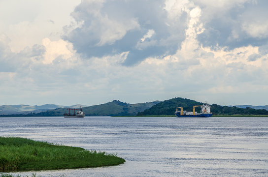 Container cargo ships on mighty Congo river with dramatic cloudy sky and lush green grass in foreground, DRC, Africa