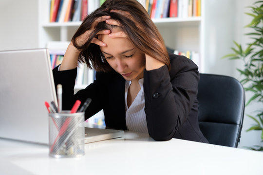 Tired and stressed employee at work sitting in the office