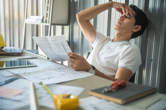 Feeling exhausted. Young architect massaging his nose and keeping eyes closed while sitting at his working place in office.