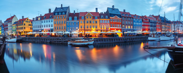 Wall Mural - Panorama of north side of Nyhavn with colorful facades of old houses and old ships in the Old Town of Copenhagen, capital of Denmark.