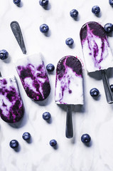 Blueberry coconut milk swirl popsicles with lime on marble background.