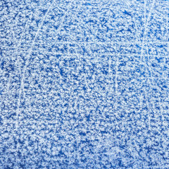 Patterns of natural hoarfrost on glass on a blue background. winter frost background, texture