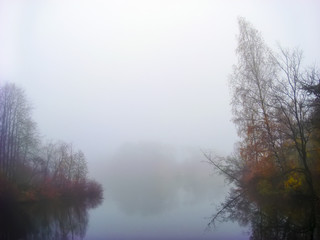 Colorful view with a forest in mistic fog in the morning, lake at dawn with clouds reflected in the calm water