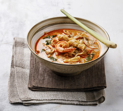 Tom Yam kung Spicy Thai seafood soup with shrimp, coconut milk and lemon grass in bowl