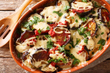 Summer recipe for eggplant casserole with tomatoes, herbs and cheese close-up in a baking dish. Horizontal top view