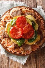 Tasty Lebanese recipe maklouba: rice with beef, eggplant, pepper, onions and tomatoes close-up. Vertical top view