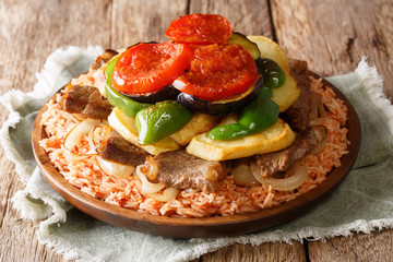Home Arabic cuisine: Maklouba or Makloubeh or Makloubi rice with beef and vegetables close-up on a plate. horizontal