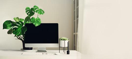 Designer workspace. Banner. Minimalistic home office. Blank screen desktop computer, Mockup desktop computer, lamp, graphics tablet, keyboard, mouse, pen, succulent plant on white desk. Copy space