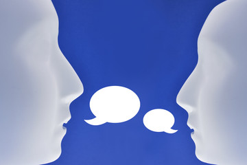 Communication of two heads stock images. Two heads silhouette. Plastic human face stock images. Plastic white face mask stock images. White mask on a blue background. Two plastic human mask