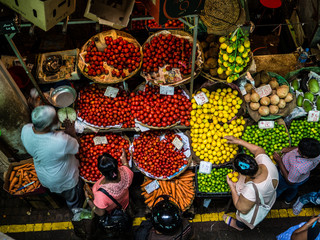 people buying food, fruit and vegetables at a stall in traditional central market in Port Louis, Mauritius