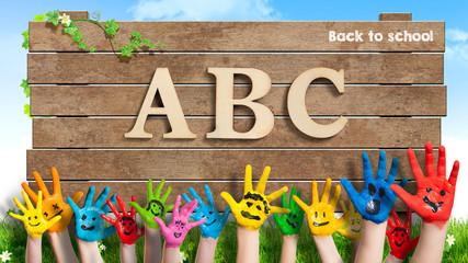 """in bunten Farben angemalte Kinderhände und Schild mit """"ABC - Back to school"""""""