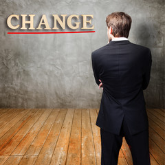 "businessman in front of a wall with the word ""change"""