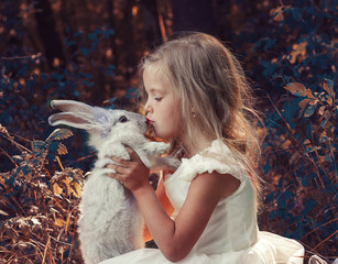 Маленькая девочка в белом платье сидит в лесу и держит в руках белого кролика.