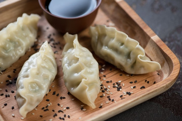 Close-up of steamed korean dumplings on a wooden serving tray, selective focus