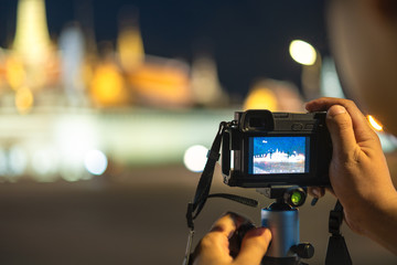 man photographer adjust camera setting for shooting light and grand palace, traveling landmark in Bangkok
