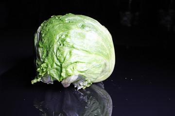 Whole iceberg Salad on black reflective background