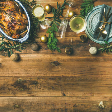 Christmas or New Year celebration table setting. Flat-lay of roast chicken, plates, silverware, glass and toy holiday decoration over rustic wooden background, top view, copy space, square crop