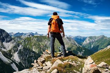 Mann genießt die Aussicht auf die Alpen vom Gipfel eines Berges