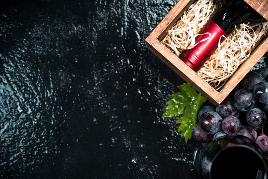 Red wine bottle in crate, border background