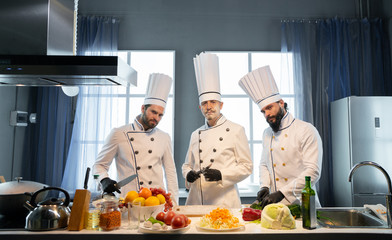 Three chefs at a restaurant near a table with food