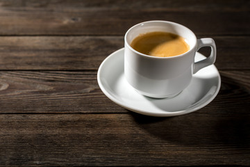 Black coffee in white cup on black wood background
