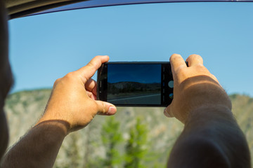 A young man pulling two hairy hands into the open window of a moving car holds a smartphone taking a photo of the mountains in the Altai with blue clear sky on an autumnal summer day during a journey