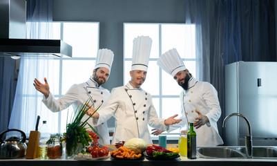 Three modern cooks in the kitchen