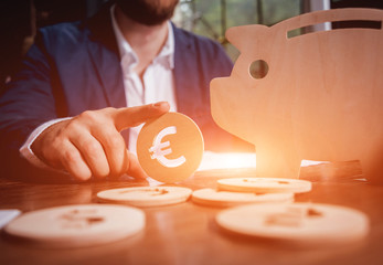 Businessman holds a coin near wooden piggy. Money box. Collecting money with earning bank.